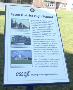 Plaque about Essex District High School staked in the ground in front of school building