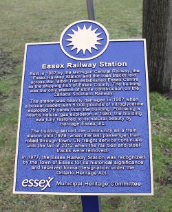 Bronze plaque with sun emblem at the top and description of Essex Railway Station below
