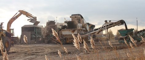 Rubble is loaded into machine that crushes and expels