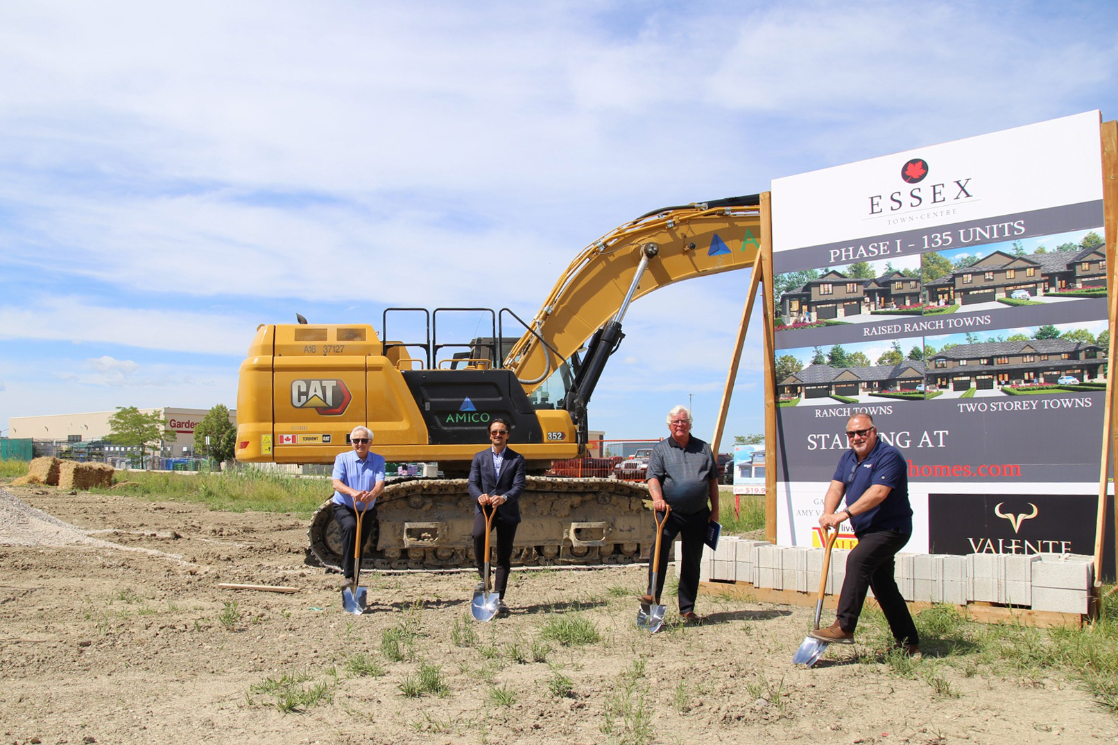 Four people with shovels in the ground at a construction site for a new residential development in the Town of Essex. A sign and backhoe are pictured in the background.