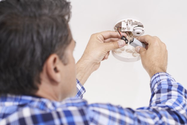 Image of man changing a carbon monoxide detector battery.