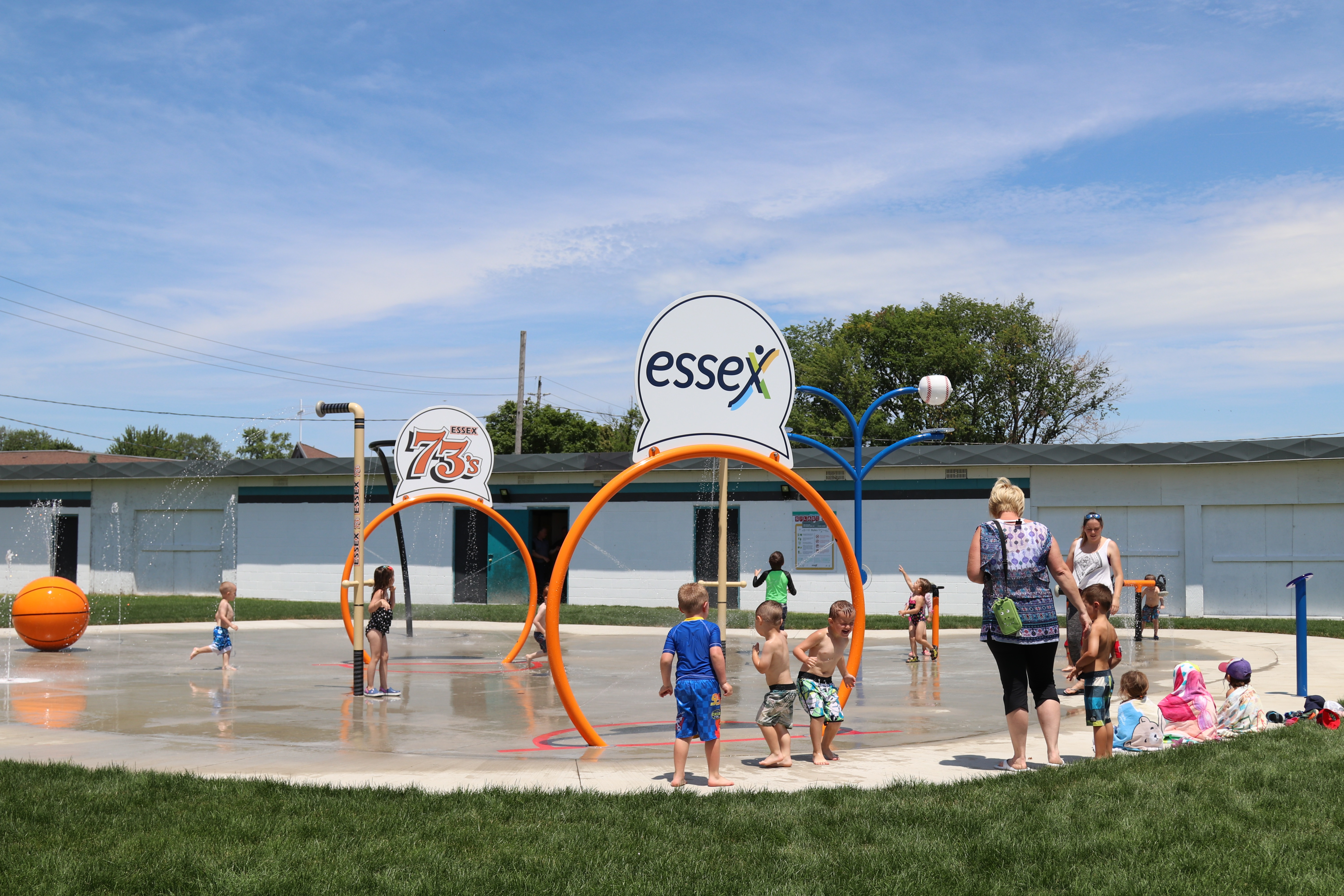 Image of grand opening of Essex Centre Splash pad. Photo shows a landscape image of the splashpad with kids and parents gathered.