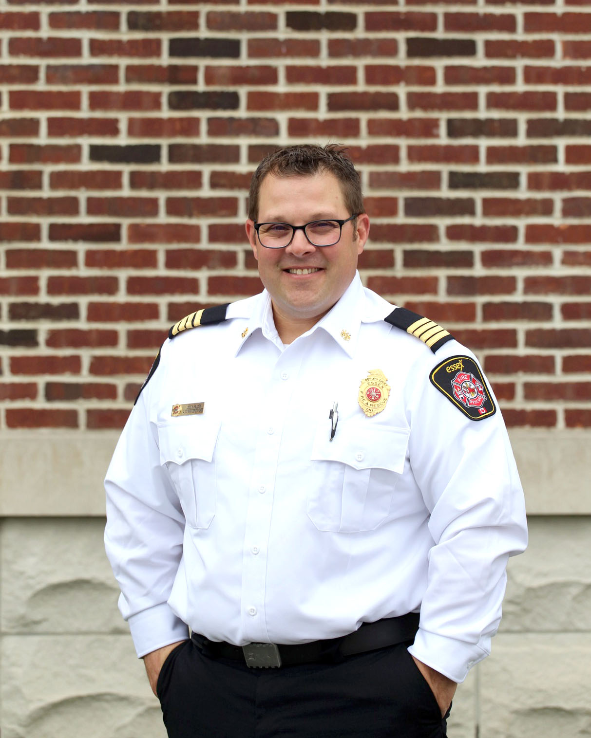 Portrait of Deputy Fire Chief Jason Pillon in white dress uniform with brick/stone wall in background.