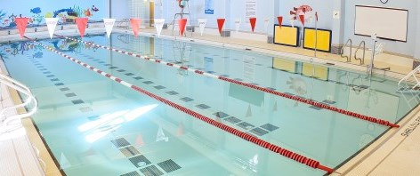 Lengths of a swimming pool with red and white flags over top
