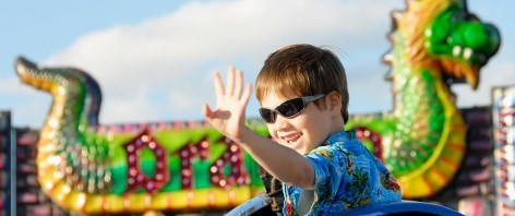 Boy on carnival ride waving his hand
