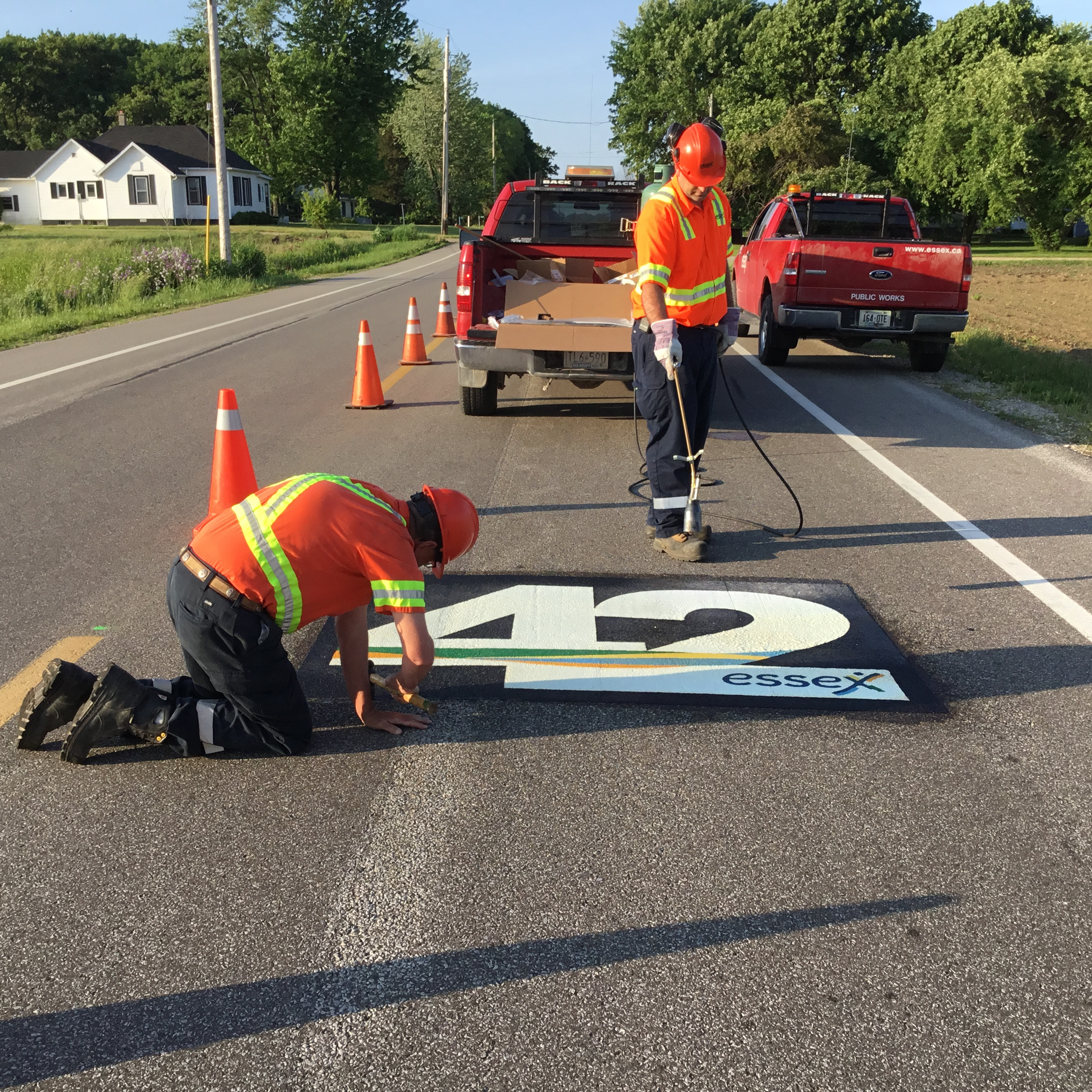 Town workers apply finishing touches to 42nd parallel road marking
