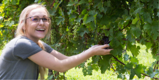 girl in vineyard smiling holding grapes