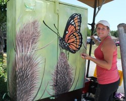 Christine Dexter paints butterfly on mildweed mural